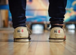 Closeup of bowling shoes being worn in front of a bowling lane