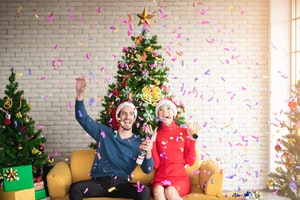 Man and woman on sofa in room of Christmas decorations with falling confetti